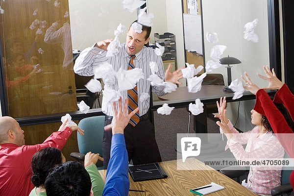 Businesspeople throwing paper at meeting