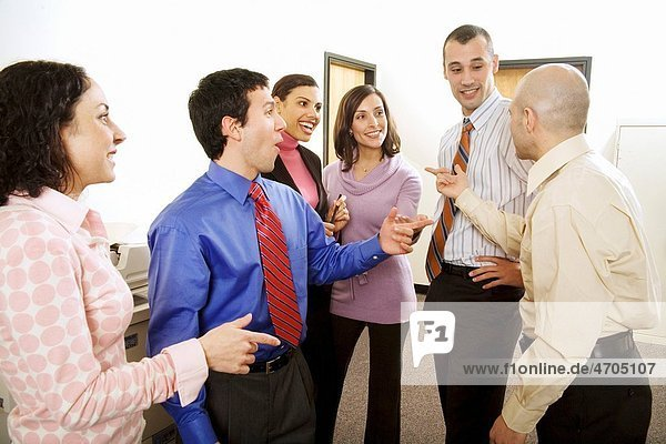 Group of co_workers talking in office