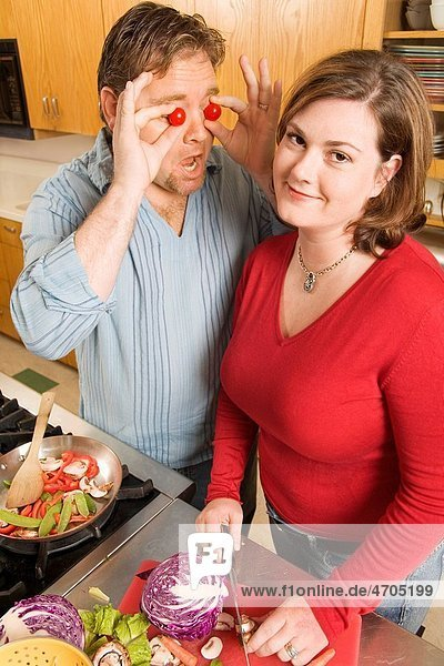 Couple playing with food while cooking