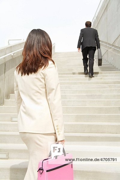 Businesspeople looking up steps