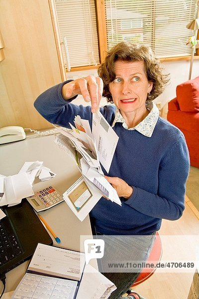 Frustrated woman sorting bills in home office