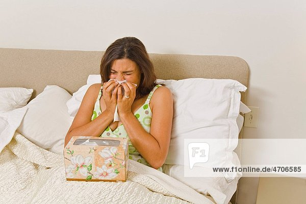 Woman blowing nose in bed