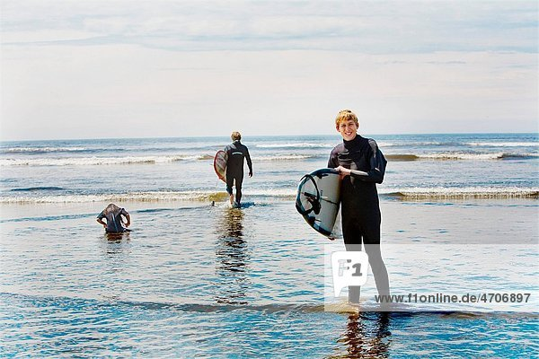 Surfers holding surfboards on the beach  Washington State  USA