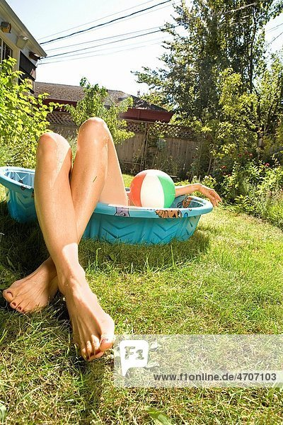 Woman lying in a wading pool