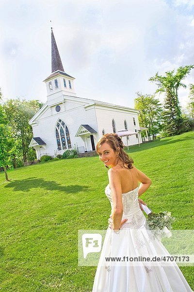 Bride standing near a church  East Meredith  New York State  USA