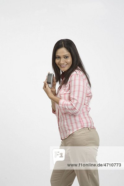 Young girl smiling holding mobile phone and showing MR 703C