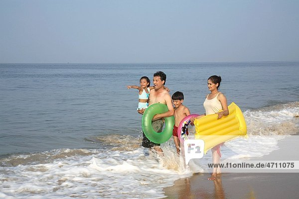 South Asian Indian parent and children holding hands standing in surf water on seashore carrying daughter   Shiroda   Dist Sindhudurga   Maharashtra   India MR703D 703E 703F 703G
