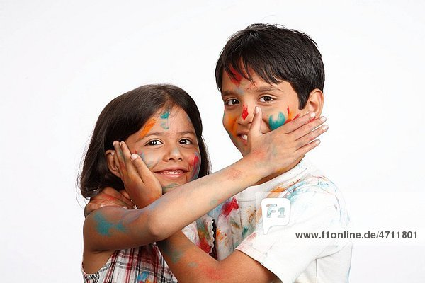 Ten and eight year old boy and girl applying colours on each other cheek on Holi festival MR703U 703V