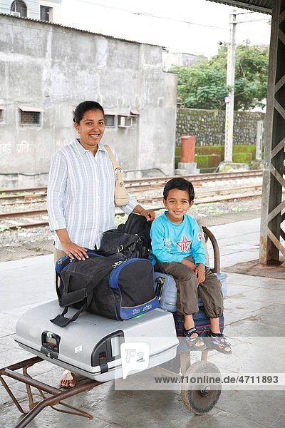 Mother standing and son sitting on baggage kept on trolley MR468