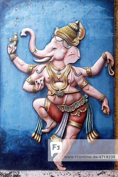 Colourfully painted relief of dancing lord Ganesh Ganpati on wall of temple Colourfully painted relief of dancing lord Ganesh Ganpati on wall of temple
