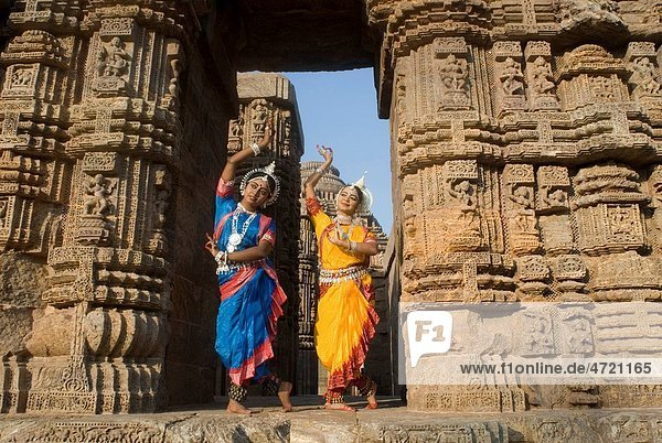 Odissi dancers strike pose re_enacts Indian myths such as Ramayana in front of world heritage Sun temple complex in Konarak   Orissa   India MR400