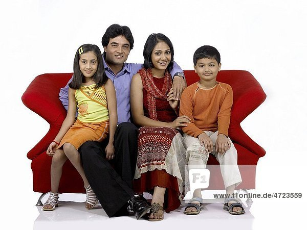 South Asian Indian family with father mother son and daughter sitting on sofa smiling and looking at camera MR 698   699   700   701