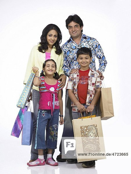 South Asian Indian family with father mother son and daughter standing with carrying shopping bags MR 698   699   700   701