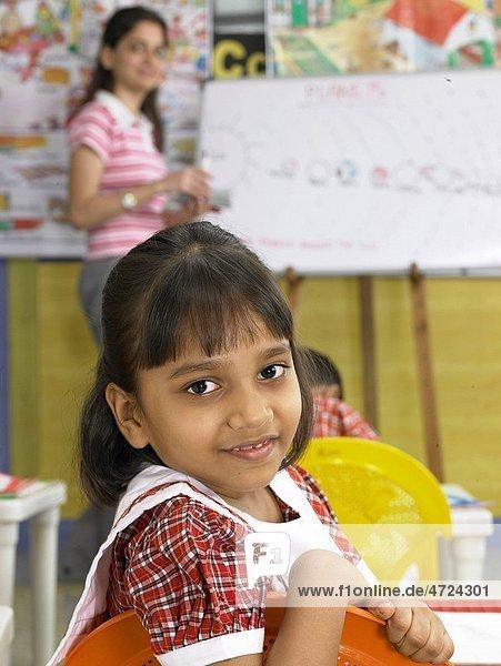 South Asian Indian girl looking behind in nursery school MR
