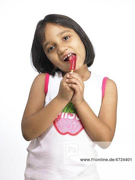 South Asian Indian girl sucking lollipop in nursery school MR