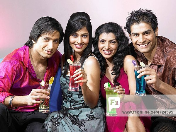 South Asian Indian men and women holding drink glasses celebrating party MR