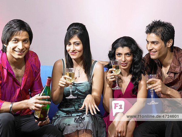 South Asian Indian men and women showing champagne glasses celebrating party MR