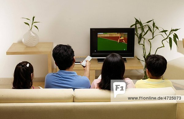 Children with parents watching match on TV sitting in house MR702R MR702S MR702T MR702U