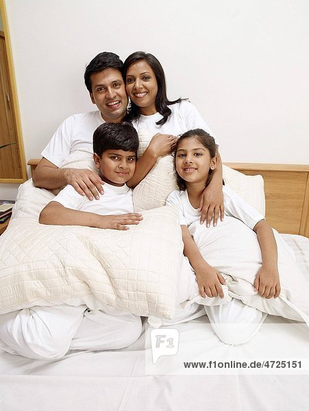Children with parents holding pillows sitting on bed in bedroom MR702R MR702S MR702T MR702U