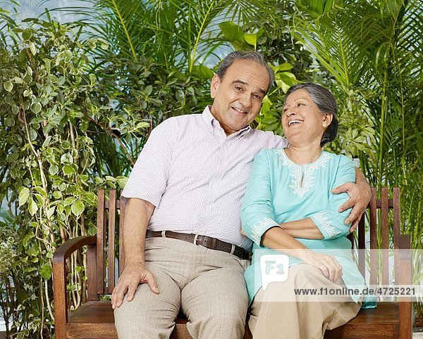 Old couple embracing sitting on wooden bench MR702T 702S