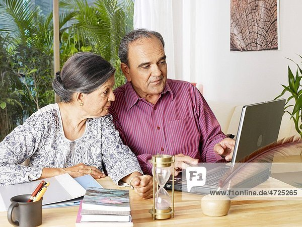 Old couple operating laptop looking at screen MR702T 702S
