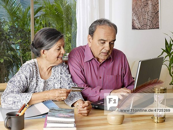 Old couple operating laptop with using credit card MR702T 702S