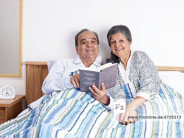 Old couple holding novel sitting on bed MR702T 702S