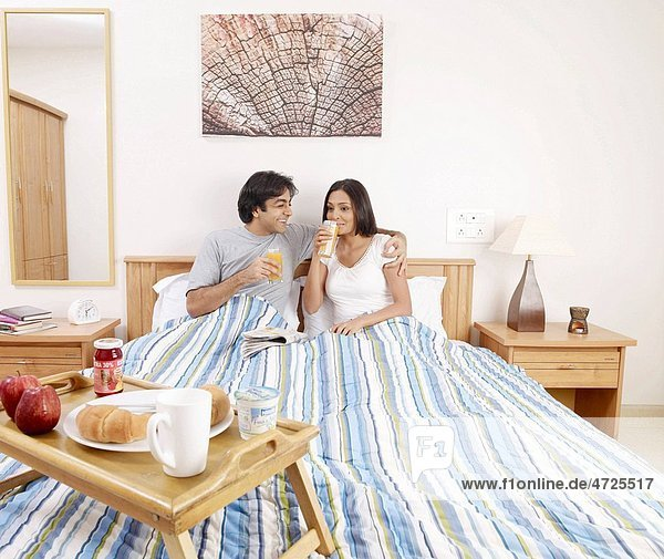 Young man and woman drinking juice having breakfast on bed MR702V 702U