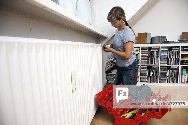 Junge Frau repariert den Thermostat an einem Heizkörper