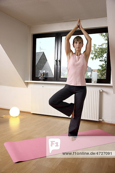 Young woman doing yoga exercises at home