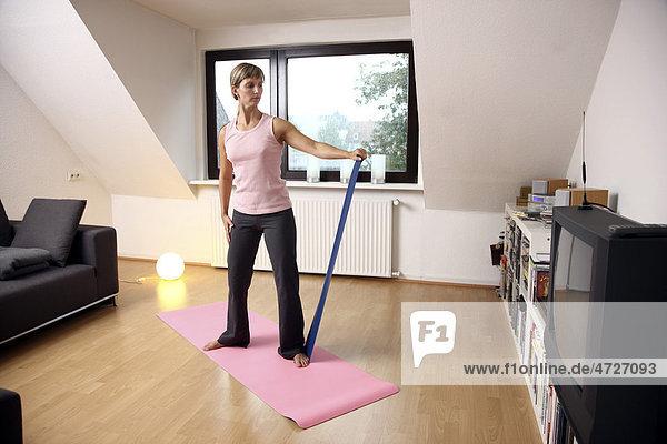 Junge Frau macht zu Hause Gymnastik mit einem Deuser-Band