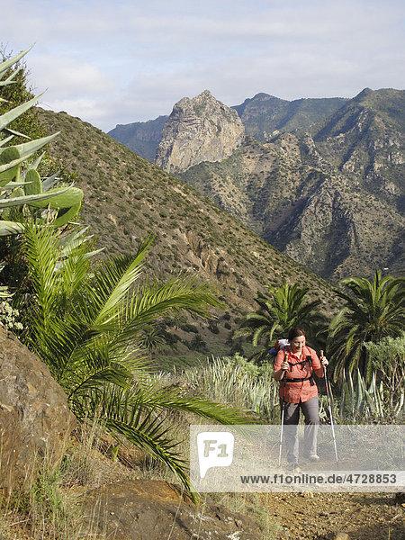 Frau mit Rucksack und Wanderstöcken  Barranco de la Era Nueva  hinten Roque Cano  Vallehermoso  La Gomera  Kanaren  Spanien  Europa