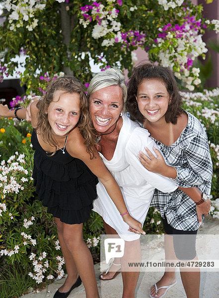 Porträt einer Mutter mit zwei dreizehnjährigen Mädchen  hinten Blumen