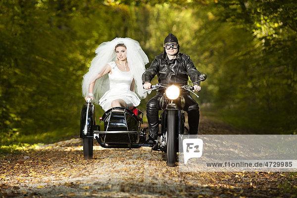 Braut und Bräutigam fahren in Motorrad mit Beiwagen zur Hochzeit