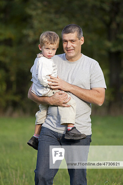 Father carrying his young son in his arms