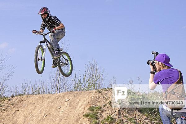 Junger Biker springt mit Bike und wird fotografiert