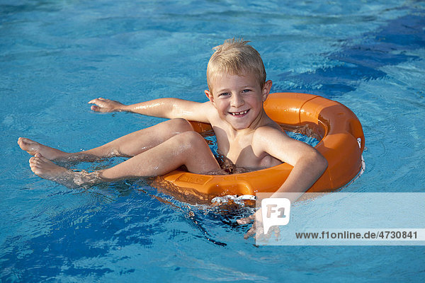 Boy  7  in a pool on a life ring