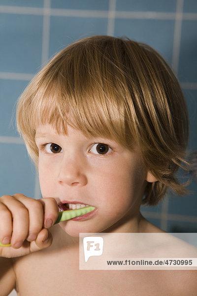 Vierjähriger blonder Junge putzt seine Zähne
