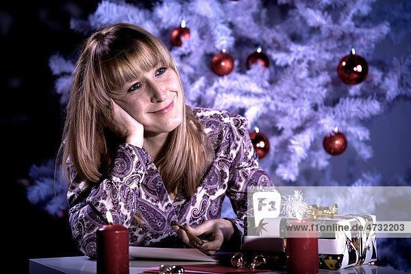 Frau schreibt Weihnachtspost vor dem Weihnachtsbaum