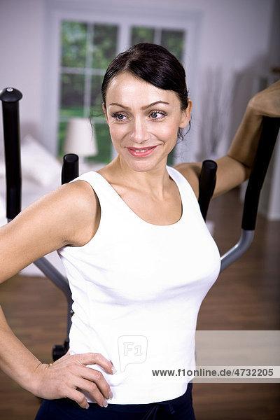 Frau vor dem Crosstrainer