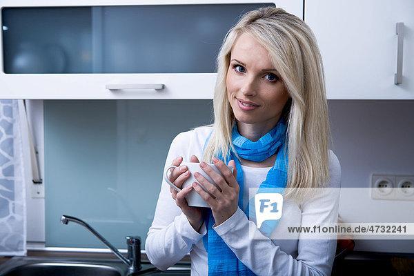 Eine junge Frau mit Teetasse in der Küche