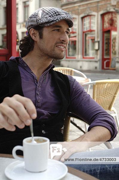 Mann Anfang dreißig in Freizeitkleidung beim Kaffeetrinken im Straßencafe  vergnügt