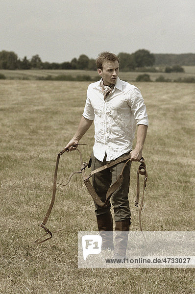 Man wearing riding clothes standing in a field in summer holding a leather strap