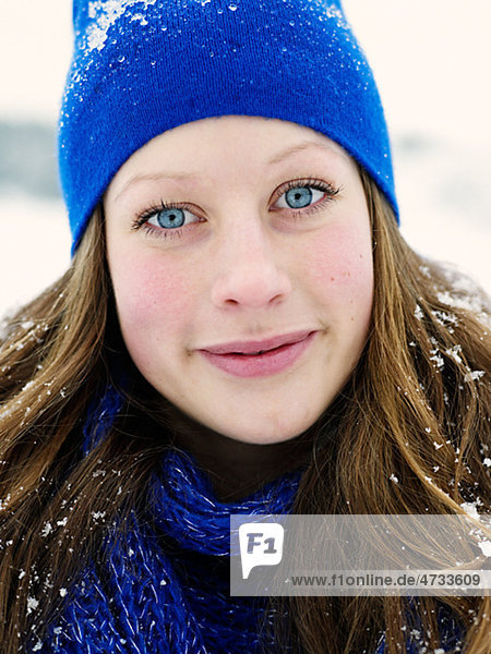 Portrait of young woman wearing blue hat and blue wooly scarf