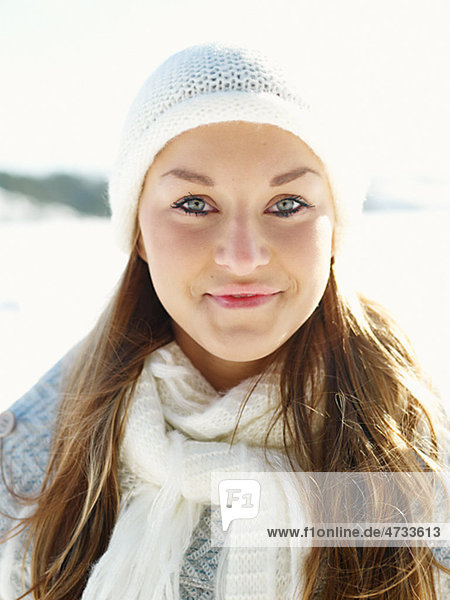 Portrait of young woman wearing white hat and white wooly scarf