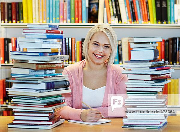 Junge Frau umgeben von Büchern in Bibliothek
