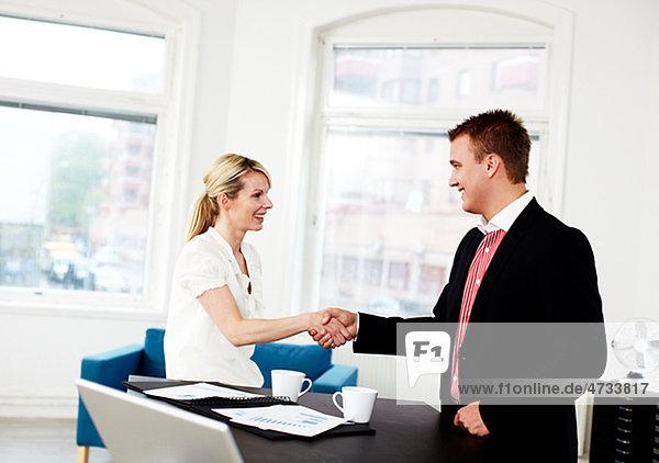 Kaufmann und Frau Händeschütteln in office