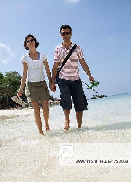 Mitte adult paar hält hände und Wandern am Strand