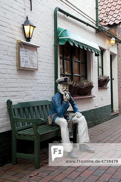Restaurant and tea room with a seated sailor figure  Greetsiel  Krummhoern  East Frisia  Lower Saxony  North Sea  Germany  Europe