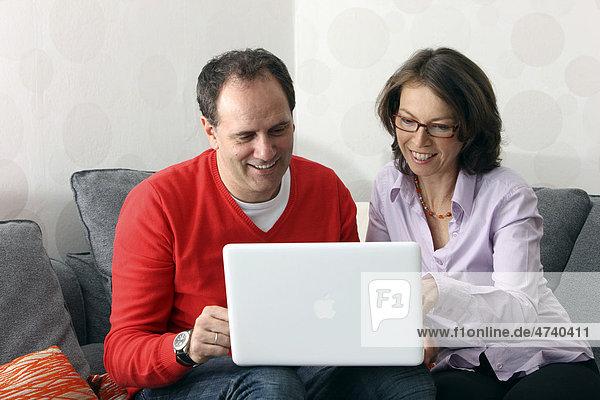 Paar  Mann  Frau  Mitte 40  zuhause beim Surfen im Internet am Laptop